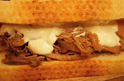 This French Dip Sandwich recipe is an easy idea for a savory family meal, or for a crowd pleasing party food. Fork tender beef is served on crusty french bread with delicious sauce and a side of au jus.