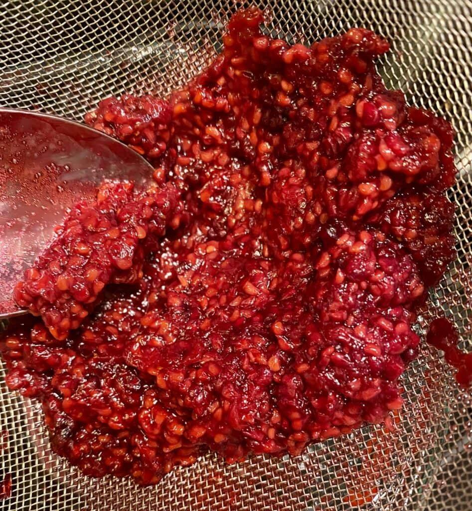 straining the sauce for seedless raspberry sauce