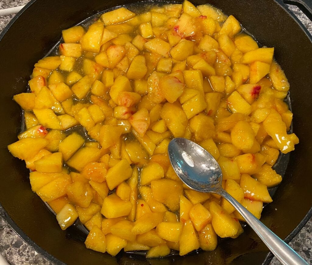 making peach cobber in a skillet with peach cobbler filling